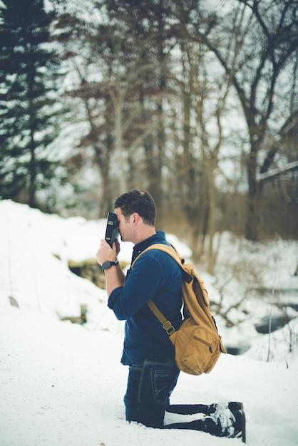 Pionowe Ujęcie Mężczyzny Na Kolanach Na Zaśnieżonej Ziemi, Trzymając Biblię Przed Głową Modlącą Się Darmowe Zdjęcia