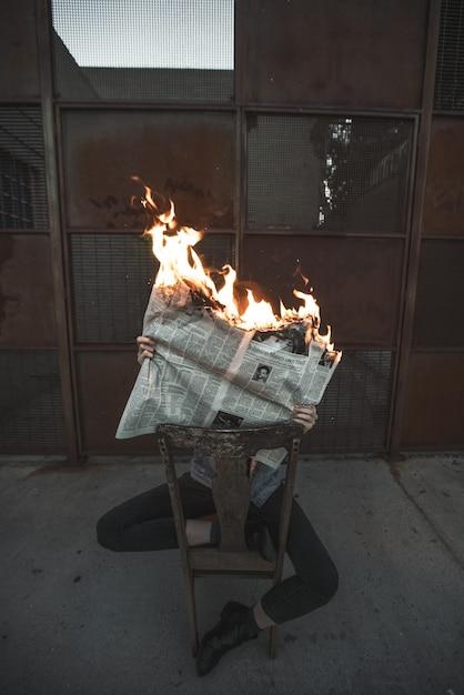 Pionowe Ujęcie Mężczyzny Siedzącego Na Krześle Czytającego Płonącą Gazetę Concept- Fałszywe Wiadomości Darmowe Zdjęcia