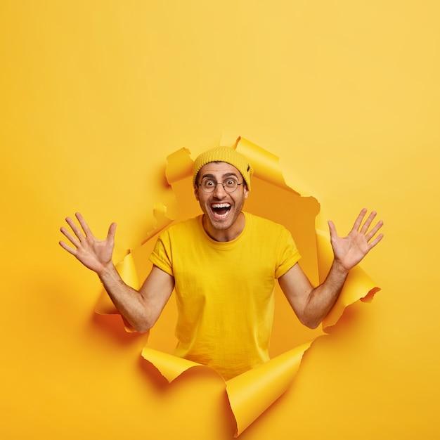 Pionowe Ujęcie Optymistycznego Człowieka Stwarzających Przez Rozdarty Papier Darmowe Zdjęcia