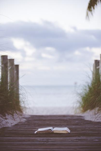 Pionowe Ujęcie Otwartej Biblii Na Drewnianej ścieżce W Kierunku Morza Z Rozmytym Tłem Darmowe Zdjęcia