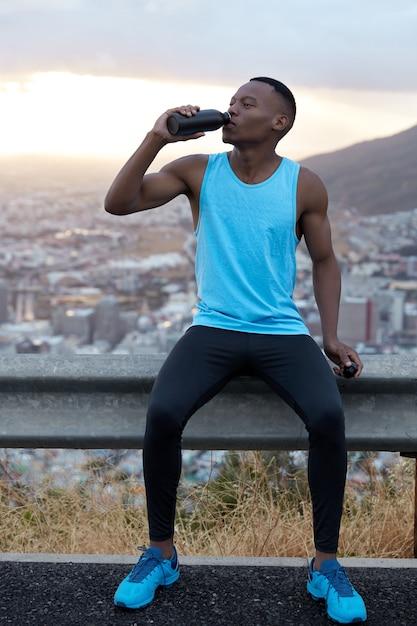 Pionowe Ujęcie Przystojnego Afroamerykanina W Sportowej Odzieży Pije Wodę Po Treningu Fitness, Odświeża Się Napojem, Pozuje Na Górskim Wzgórzu, Czuje Zmęczenie. Koncepcja Sportu I Odmładzania Darmowe Zdjęcia