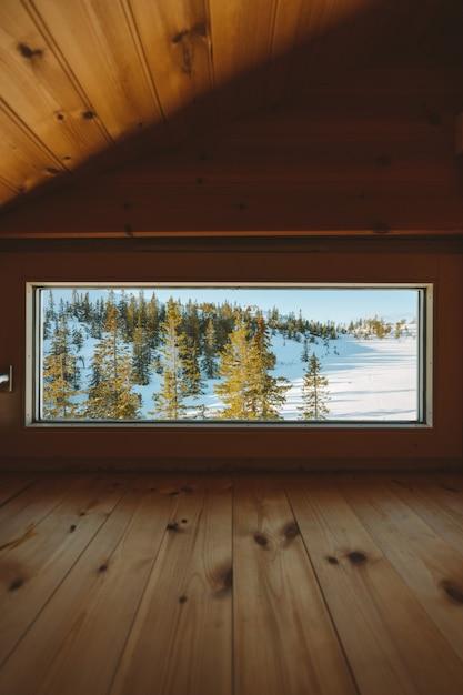 Pionowe Ujęcie Przytulnego Strychu Z Oknem Z Widokiem Na Pokryty śniegiem Las W Norwegii Darmowe Zdjęcia