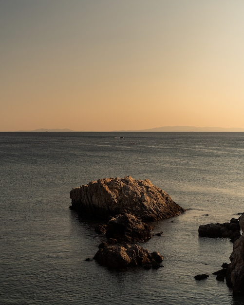 Pionowe Ujęcie Skał O Różnych Rozmiarach W Morzu Pod Bezchmurnym Niebem Darmowe Zdjęcia