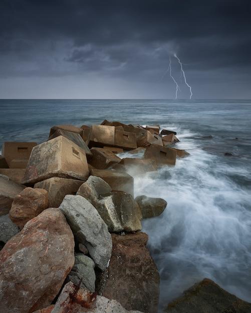 Pionowe Ujęcie Skał W Morzu Podczas Burzy I Błyskawic Darmowe Zdjęcia