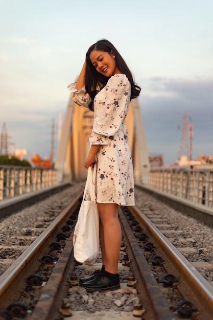 Pionowe Ujęcie Wietnamskiej Dziewczyny Stojącej Na Torach Kolejowych Starego Mostu Darmowe Zdjęcia