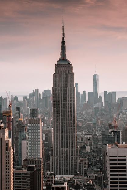 Pionowe Ujęcie Wieżowca Otoczonego Budynkami Miasta Z Pięknym Niebem Darmowe Zdjęcia