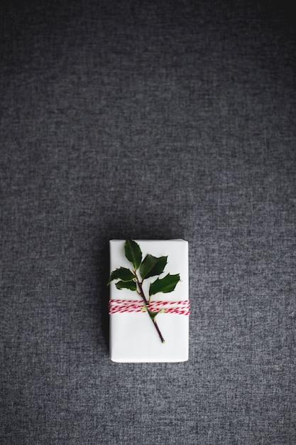 Pionowe Ujęcie Z Góry Białego świątecznego Pudełka Ozdobionego Małą Gałązką Z Zielonymi Liśćmi Darmowe Zdjęcia