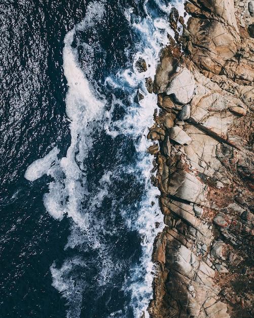 Pionowe Ujęcie Z Góry Skalistej Linii Brzegowej Obok Akwenu Z Falami Pluskającymi Skały Darmowe Zdjęcia