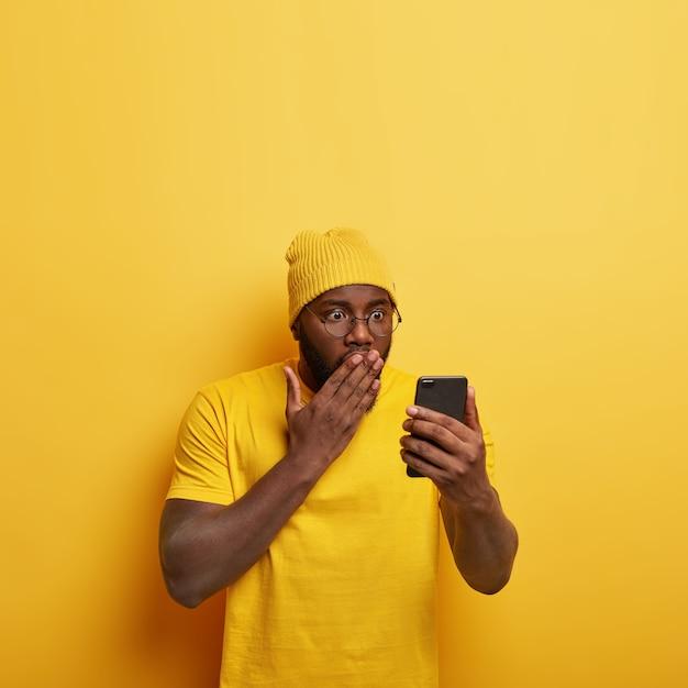 Pionowe Ujęcie Zawstydzonego Przystojnego Faceta W Okularach Z Jego Telefonem Darmowe Zdjęcia