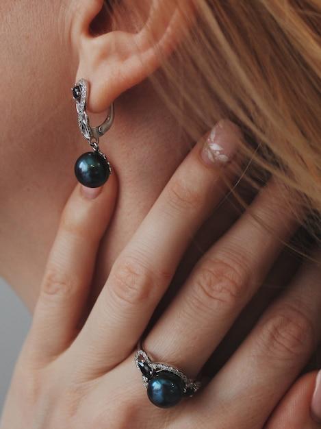 Pionowe Zbliżenie Strzał Kobiety Noszącej Pierścień I Kolczyki Z Czarnym Wisiorkiem Darmowe Zdjęcia