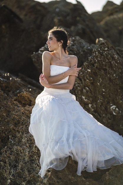 Pionowe Zdjęcie Brunetki Kobiety W Białej Sukni Pozującej Na Skałach Darmowe Zdjęcia