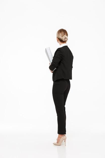 Pionowo Tylny Widok Blondynki Biznesowa Kobieta Trzyma Dużą Falcówkę Nad Biel ścianą Darmowe Zdjęcia