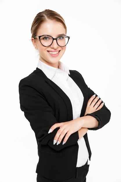 Pionowo Wizerunek Uśmiechniętej Blondynki Biznesowa Kobieta W Eyeglasses Pozować Z Ukosa Z Krzyżować Rękami Nad Bielem Darmowe Zdjęcia