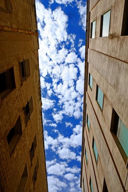 Pionowy Niski Kąt Strzału Z Dwóch Budynków Z Pochmurnego Nieba Darmowe Zdjęcia