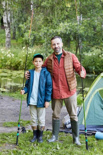 Pionowy Portret Pełnej Długości Szczęśliwego Ojca I Syna, Którzy Wspólnie łowią Ryby I Podczas Wyprawy Nad Jezioro Premium Zdjęcia