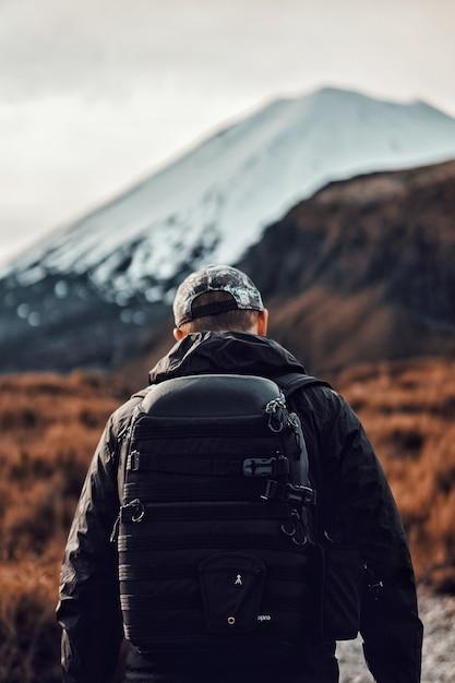 Pionowy Widok Mężczyzny W Czerni Z Plecakiem Wędrującym W Pobliżu Pięknych Gór Darmowe Zdjęcia