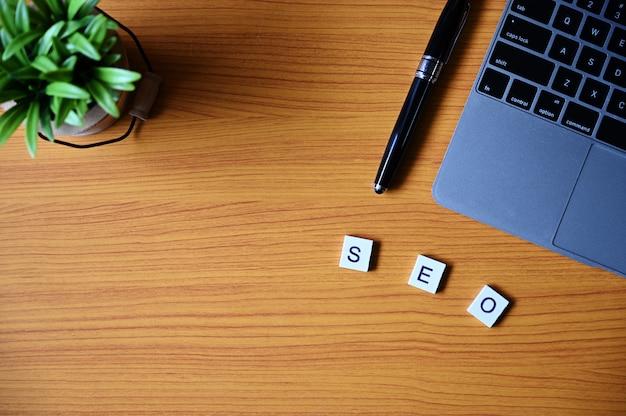 Pióro, Laptop, Rośliny I Drewniane Kwadraty Tworzące Słowo Na Drewnianym Stole Premium Zdjęcia