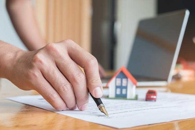 Pióro Obsługuje Podpisane Dokumenty Z Modelowymi Domami, Modelem Samochodu I Laptopem Na Stole. Premium Zdjęcia