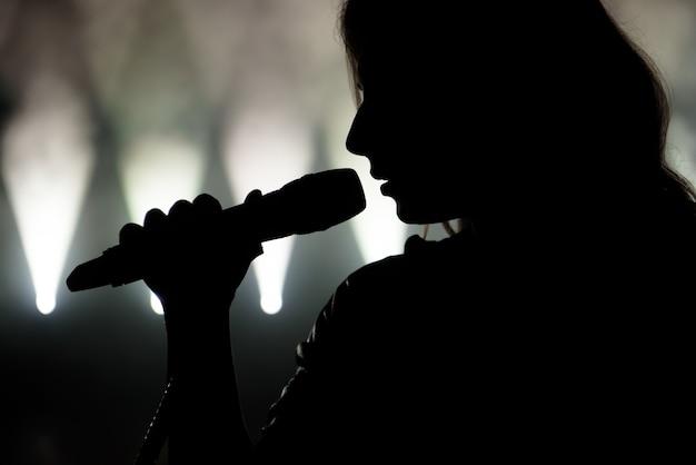 Piosenkarka W Sylwetce. Zamknij Się Obraz Piosenkarki Na żywo Na Scenie Premium Zdjęcia