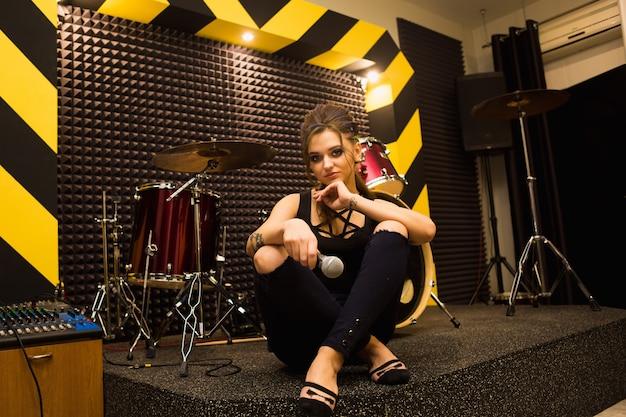 Piosenkarz Rockowy Nagrywający Dźwięk W Profesjonalnym Studio Z Mikrofonem Na Pasiastej ścianie Premium Zdjęcia