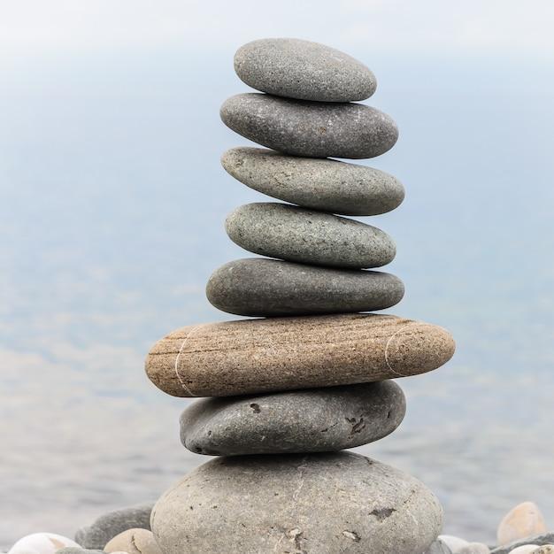 Piramida z kamieni morskich na kamyki brzegu morza. Premium Zdjęcia