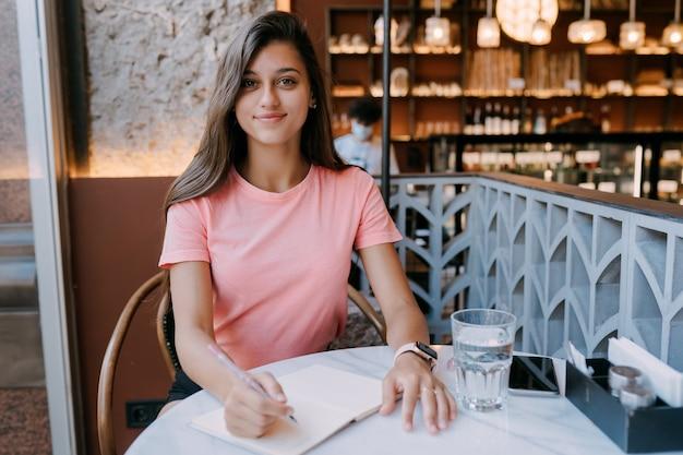 Pisanie Nabiału W Notatce W Kawiarni, Koncepcja Jako Pamięć życia. Kobieta W Kawiarni. Uśmiechnięta Kobieta Robi Notatki Notatnik. Darmowe Zdjęcia