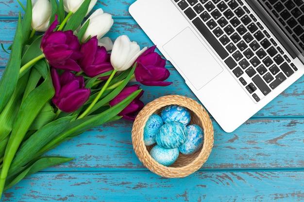 Pisanki, makieta laptopa i bukiet tulipanów. Premium Zdjęcia