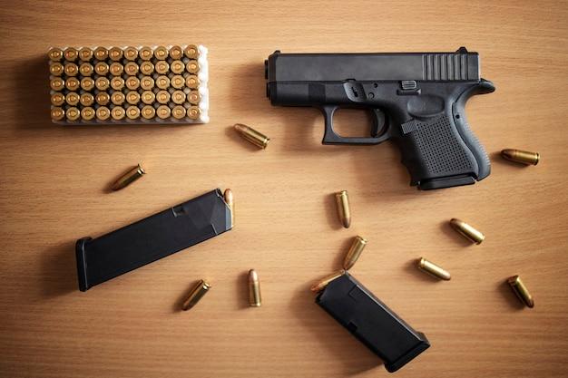 Pistolet Z Pudełkiem Amunicji I Kul Na Drewnianej ścianie Darmowe Zdjęcia