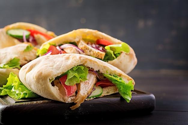 Pita faszerowana kurczakiem, pomidorem i sałatą na drewnianej, bliskowschodniej kuchni. Premium Zdjęcia