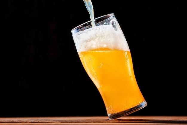 Piwo Leje Do Szklanki Na Ciemnym Tle Premium Zdjęcia