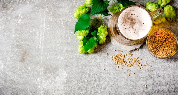 Piwo, Zielony Chmiel I Słód Na Kamiennej Powierzchni. Widok Z Góry Premium Zdjęcia