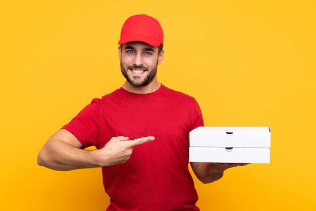 Pizza Dostawa Człowiek W Mundurze Roboczym, Zbierając Pudełka Po Pizzy Na Pojedyncze żółte ściany I Wskazując Go Premium Zdjęcia