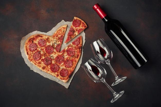 Pizza w kształcie serca z mozzarellą, kiełbasą i butelką wina. Premium Zdjęcia