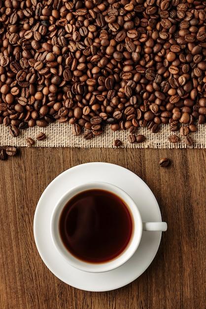Płaska Kompozycja Z Filiżanką Gorącej Kawy I Ziaren Kawy Premium Zdjęcia
