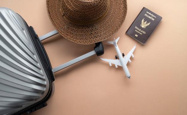 Płaska leżąca szara walizka z brązowym kapeluszem, mini samolotem i paszportem tajlandii Premium Zdjęcia