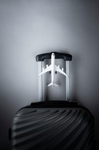 Płaska leżąca szara walizka z mini samolotem. koncepcja podróży Premium Zdjęcia