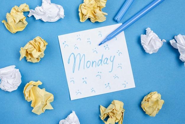 Płaski Karteczkę Z Marszczonymi Brwiami I Pognieciony Papier Na Niebieski Poniedziałek Darmowe Zdjęcia