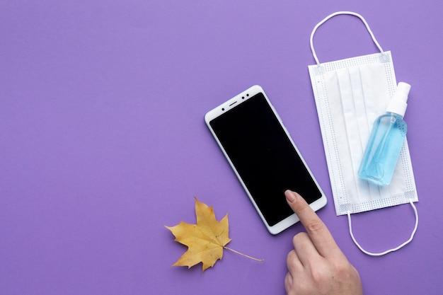 Płaski Układ Dłoni Za Pomocą Smartfona Z Maską Medyczną I Jesiennym Liściem Darmowe Zdjęcia