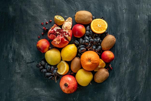 Płaski układ świec świeżych owoców na powierzchni grunge, takich jak winogrona, kiwi, pomarańcza, egzotyczne owoce tropikalne Premium Zdjęcia