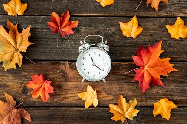 Płaski zegar centrowany z kolorowymi liśćmi Darmowe Zdjęcia