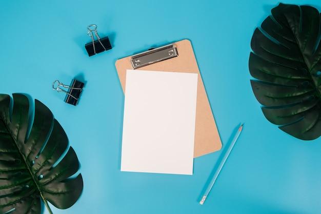 Płaskie lay makieta papieru a4 ze schowka, liści palmowych i ołówek na niebieskim tle. Premium Zdjęcia