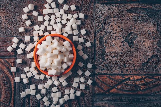 Płaskie Leżały Kostki Cukru Białego W Pomarańczowej Misce Na Ciemnym Drewnianym Stole. Poziomy Darmowe Zdjęcia