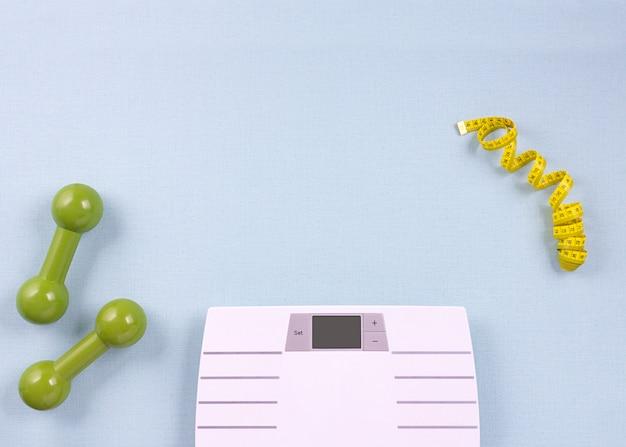 Płaskie skład świeckich przedmiotów sportowych, skaluje na niebieskim tle. koncepcja utraty wagi. widok z góry, miejsce na kopię. Premium Zdjęcia