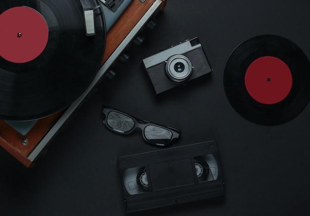 Płaskie świeckie Media I Rozrywka W Stylu Retro. Gramofon Z Płytą Winylową, Kamerą Filmową, Kasetą Wideo Na Czarnym Tle. 80s. Widok Z Góry Premium Zdjęcia