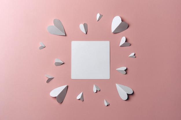 Płaskie Ukształtowanie Białej Pustej Makiety Z Papierowymi Sercami Na Różowym Tle. Premium Zdjęcia