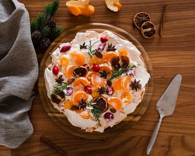 Płaskie Ukształtowanie Ciasta Bezowego Ozdobione Plasterkami Pomarańczy I Dzikiej Róży Darmowe Zdjęcia
