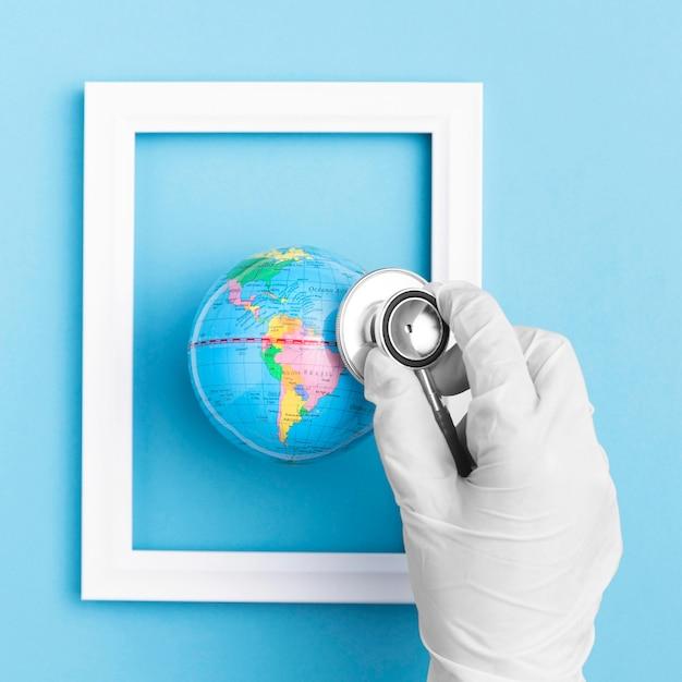 Płaskie Ukształtowanie Dłoni Z Rękawic Chirurgicznych Gospodarstwa Stetoskop Nad Globusem Ziemi W Ramce Darmowe Zdjęcia