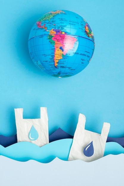 Płaskie Ukształtowanie Globu Ziemi Z Papierowymi Falami Oceanu I Plastikowymi Torbami Darmowe Zdjęcia