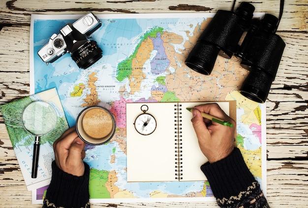 Płaskie Ukształtowanie Koncepcji Planowania Podróży. Widok Z Góry Rąk Człowieka Piszącego Na Dzienniku, Na Stole Lornetka, Kompas, Aparat Fotograficzny Retro, Kawa I Mapa Europy Na Białym Drewnianym Stole Premium Zdjęcia