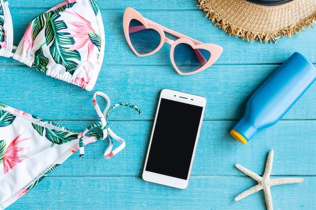 Płaskie Ukształtowanie Letnich Przedmiotów Z Kolorowym Bikini, Smartfonem, Okularami Przeciwsłonecznymi, Kapeluszem Plażowym, Kremem Do Opalania I Smartfonem Premium Zdjęcia